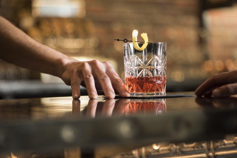 bartender serving a sazerac cocktail in old fashioned glass with lemon twist