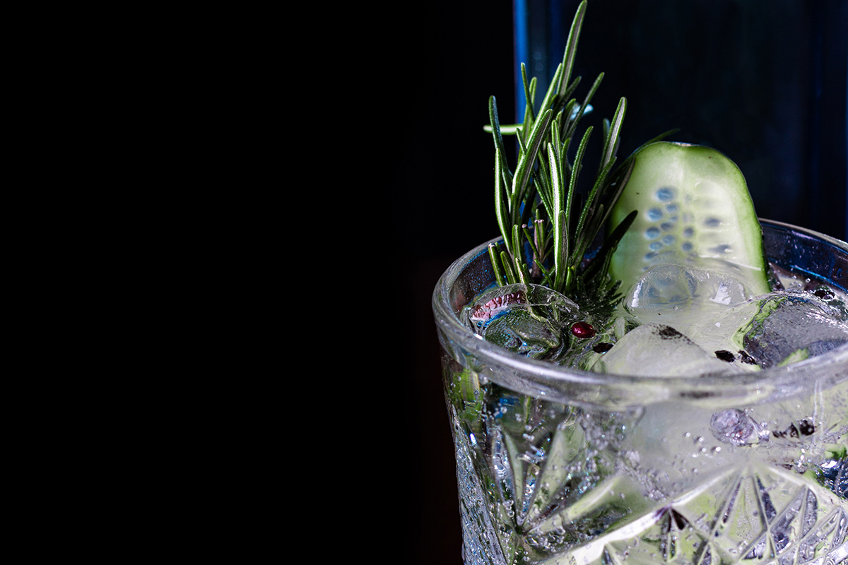 cucumber gimlet in cocktail glass over ice garnished with rosemary and cucumber