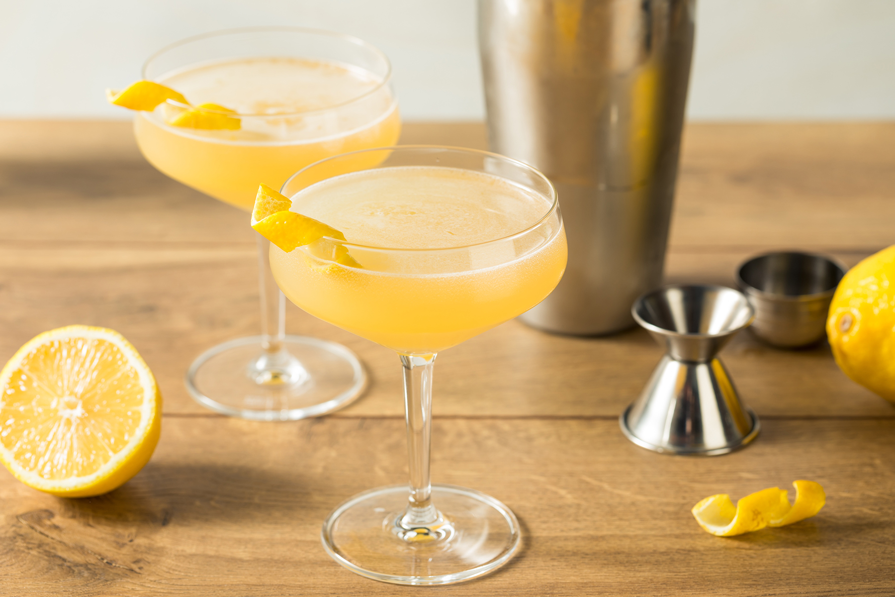 two corpse reviver cocktails in coupe glasses with jigger and mixing tin and lemon pieces
