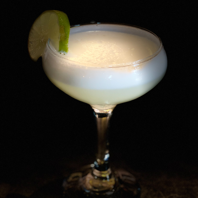 a brandy sour with frothy egg white in a cocktail glass with lime wedge garnish